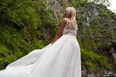 Ένα νέο ξανθό κορίτσι που στέκεται με την πίσω σε ένα άσπρο φόρεμα μπουντουάρ στα βουνά σε ένα κλίμα ενός καταρράκτη και στοκ εικόνες