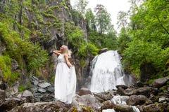 Ένα νέο ξανθό κορίτσι που στέκεται σε μια μισό-στροφή, που ισιώνει την τρίχα σε ένα φόρεμα μπουντουάρ στα βουνά ενάντια σε έναν κ στοκ φωτογραφίες με δικαίωμα ελεύθερης χρήσης