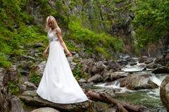 Ένα νέο ξανθό κορίτσι που στέκεται σε μια μισό-στροφή και που εξετάζει κάτω hem ενός φορέματος μπουντουάρ στα βουνά ενάντια σε έν στοκ εικόνες