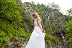 Ένα νέο ξανθό κορίτσι που στέκεται σε ένα χέρι μισό-στροφής ισιώνει ένα φόρεμα μπουντουάρ στα βουνά ενάντια σε έναν καταρράκτη κα στοκ φωτογραφία με δικαίωμα ελεύθερης χρήσης