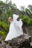 Ένα νέο ξανθό κορίτσι σε έναν κομψό θέτει ρίχνει επάνω hem ενός φορέματος μπουντουάρ στα βουνά ενάντια σε έναν καταρράκτη και μια στοκ φωτογραφίες