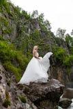 Ένα νέο ξανθό κορίτσι σε έναν κομψό θέτει ρίχνει επάνω hem ενός φορέματος μπουντουάρ στα βουνά ενάντια σε έναν καταρράκτη και μια στοκ εικόνες