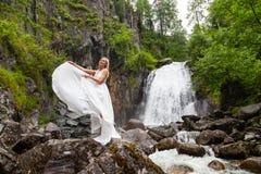 Ένα νέο ξανθό κορίτσι σε έναν κομψό θέτει ρίχνει επάνω hem ενός φορέματος μπουντουάρ στα βουνά ενάντια σε έναν καταρράκτη και μια στοκ εικόνα με δικαίωμα ελεύθερης χρήσης