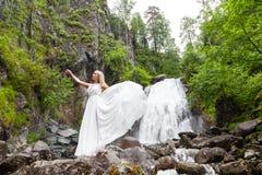 Ένα νέο ξανθό κορίτσι σε έναν κομψό θέτει σηκώνει ένα φόρεμα μπουντουάρ στα βουνά ενάντια σε έναν καταρράκτη και τις πέτρες αυξάν στοκ εικόνα