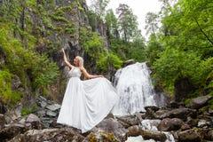 Ένα νέο ξανθό κορίτσι σε έναν κομψό θέτει σηκώνει ένα φόρεμα μπουντουάρ στα βουνά ενάντια σε έναν καταρράκτη και τις πέτρες αυξάν στοκ εικόνα με δικαίωμα ελεύθερης χρήσης