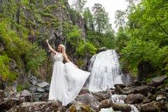 Ένα νέο ξανθό κορίτσι σε έναν κομψό θέτει σηκώνει ένα φόρεμα μπουντουάρ στα βουνά ενάντια σε έναν καταρράκτη και τις πέτρες αυξάν στοκ φωτογραφίες με δικαίωμα ελεύθερης χρήσης