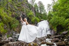 Ένα νέο ξανθό κορίτσι σε έναν κομψό θέτει σηκώνει ένα φόρεμα μπουντουάρ στα βουνά ενάντια σε έναν καταρράκτη και τις πέτρες αυξάν στοκ εικόνες με δικαίωμα ελεύθερης χρήσης