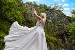 Ένα νέο ξανθό κορίτσι σε έναν κομψό θέτει σηκώνει ένα φόρεμα μπουντουάρ επάνω στα βουνά ενάντια σε έναν καταρράκτη και τις πέτρες στοκ φωτογραφίες