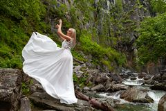 Ένα νέο ξανθό κορίτσι σε έναν κομψό θέτει σηκώνει ένα φόρεμα μπουντουάρ επάνω στα βουνά ενάντια σε έναν καταρράκτη και τις πέτρες στοκ φωτογραφίες με δικαίωμα ελεύθερης χρήσης