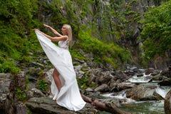 Ένα νέο ξανθό κορίτσι σε έναν κομψό θέτει σηκώνει ένα φόρεμα μπουντουάρ στα βουνά ενάντια σε έναν καταρράκτη και τις πέτρες αυξάν στοκ φωτογραφία με δικαίωμα ελεύθερης χρήσης