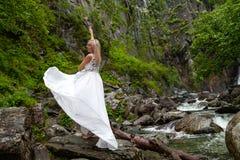 Ένα νέο ξανθό κορίτσι σε έναν κομψό θέτει σηκώνει ένα φόρεμα μπουντουάρ στα βουνά ενάντια σε έναν καταρράκτη και τις πέτρες αυξάν στοκ εικόνες