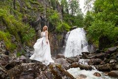 Ένα νέο ξανθό κορίτσι σε έναν κομψό θέτει τη λαβή hem όπλων ενός φορέματος μπουντουάρ στα βουνά ενάντια σε έναν καταρράκτη και έν στοκ εικόνες
