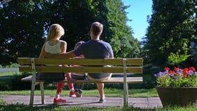 Ένα νέο παντρεμένο ζευγάρι με ένα παιδί που φιλά σε έναν πάγκο σε ένα πάρκο πόλεων φιλμ μικρού μήκους