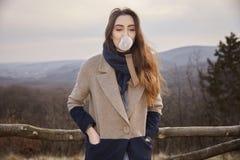 ένα νέο χαριτωμένο καυκάσιο κορίτσι, που κοιτάζει μακριά, φυσώντας γόμμα φυσαλίδων, Στοκ Εικόνες