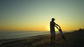 Ένα νέο όμορφο άτομο περπατά με τη μικρή κόρη του κατά μήκος της ακτής στο ηλιοβασίλεμα Ο μπαμπάς παίρνει την κόρη στα όπλα του απόθεμα βίντεο