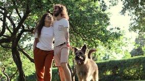 Ένα νέο όμορφο αγαπώντας ζεύγος που περπατά στο πάρκο με το σκυλί τους απόθεμα βίντεο