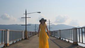 Ένα νέο όμορφο κορίτσι σε ένα κίτρινο φόρεμα περπατά κατά μήκος της αποβάθρας Θάλασσα Ωκεανός απόθεμα βίντεο