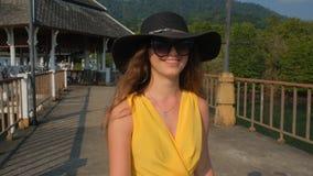 Ένα νέο όμορφο κορίτσι σε ένα κίτρινο φόρεμα περπατά κατά μήκος της αποβάθρας Θάλασσα Ωκεανός φιλμ μικρού μήκους