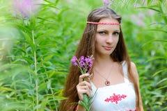 3ceb250e085f Ένα νέο όμορφο σλαβικό κορίτσι με μακρυμάλλη και ένα σλαβικό εθνικό φόρεμα  στέκεται μεταξύ του ψηλού