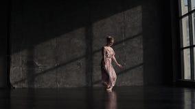 Ένα νέο όμορφο ballerina στα παπούτσια pointe και ένα μακρύ κυματίζοντας φόρεμα κινείται κομψά και χορεύει κίνηση αργή απόθεμα βίντεο