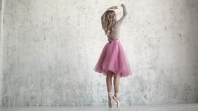 Ένα νέο ballerina σε ένα ρόδινο κλασικό πακέτο και pointe τα παπούτσια χορεύει χαριτωμένα ομορφιά και επιείκεια του μπαλέτου απόθεμα βίντεο