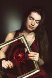 Ένα νέο brunette που κρατά ένα λουλούδι στο πλαίσιο Στοκ φωτογραφίες με δικαίωμα ελεύθερης χρήσης
