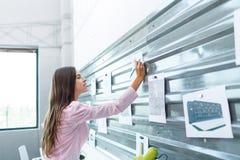 Ένα νέο brunette προσέχει τις σημειώσεις για τον τοίχο που συνδέεται με έναν μαγνήτη Στοκ Εικόνες