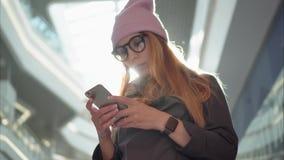 Ένα νέο hipster θηλυκό χρησιμοποιώντας app στο smartphone στη μεγάλη λεωφόρο Στοκ Εικόνες