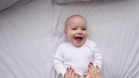 Ένα νεογέννητο μωρό που βρίσκεται στο κρεβάτι, εξετάζοντας τη κάμερα και γύρω σε ένα άσπρο σεντόνι, άποψη άνωθεν Το νήπιο ξέρει φιλμ μικρού μήκους