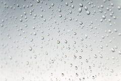 ένα νερό μειώνεται στο γκρίζο υπόβαθρο Μακροεντολή Στοκ Εικόνα