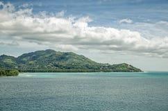 Ένα νησί με τους πράσινους λόφους, το μπλε νερό γύρω και τα μεγάλα σύννεφα ανωτέρω Στοκ Εικόνες