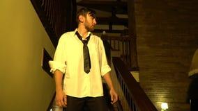Ένα νυσταλέο άτομο σε ένα κοστούμι κατεβαίνει τα σκαλοπάτια, σε αργή κίνηση απόθεμα βίντεο