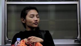 Ένα νυσταλέο κορίτσι είναι στο τραίνο απόθεμα βίντεο