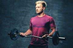 Ένα ξανθό, αθλητικό αρσενικό που ντύνεται κόκκινο sportswear κρατά το βάρβο Στοκ εικόνα με δικαίωμα ελεύθερης χρήσης