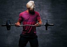 Ένα ξανθό, αθλητικό αρσενικό που ντύνεται κόκκινο sportswear κρατά το βάρβο Στοκ φωτογραφία με δικαίωμα ελεύθερης χρήσης
