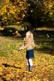Ένα ξανθό ευτυχές κορίτσι που ρίχνει επάνω στα φύλλα Στοκ εικόνα με δικαίωμα ελεύθερης χρήσης