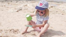 Ένα ξανθό παιδί παίζει με την άμμο στην παραλία φιλμ μικρού μήκους