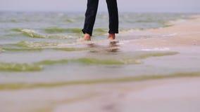 Ένα ξυπόλυτο άτομο στο παντελόνι περπατά κατά μήκος της ακτής Το νερό πλένει τα πόδια του Όνειρο της έννοιας διακοπών φιλμ μικρού μήκους