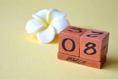 Ένα ξύλινο διαρκές ημερολόγιο με στις 8 Μαρτίου και ένα λευκό με το κίτρινο λουλούδι σε ένα κίτρινο υπόβαθρο με το διάστημα αντιγ στοκ εικόνα