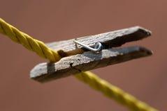 Ένα ξύλινο Clothespin που ψαλιδίζεται στη σκοινί για άπλωμα στοκ φωτογραφία