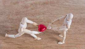 Ένα ξύλινο άτομο κουκλών σε ένα θέμα βαλεντίνων παρουσιάζει αγάπη του στο ζεύγος του Στοκ Φωτογραφία