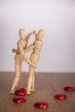 Ένα ξύλινο άτομο κουκλών στην ημέρα βαλεντίνων Παρουσίαση αγάπης στο ξύλινο πάτωμα με τη ζεστασιά Στοκ Φωτογραφίες