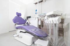 Ένα οδοντικό δωμάτιο χειρουργικών επεμβάσεων με μια οδοντική καρέκλα με την πορφυρή ταπετσαρία Στοκ εικόνες με δικαίωμα ελεύθερης χρήσης
