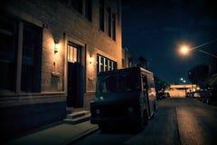 Ένα οπλισμένο φορτηγό ασφάλειας που σταθμεύουν σε ένα σκοτεινό ΝΕ οδών πόλεων τη νύχτα στοκ εικόνες