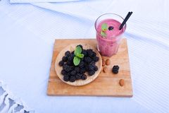 Ένα οργανικό ποτό μούρων με τη φρέσκια μέντα σε ένα μπλε υπόβαθρο υφασμάτων Ένα πιάτο με τα βατόμουρα σε ένα τέμνον γραφείο Στοκ Εικόνα