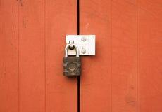 Ένα λουκέτο μετάλλων που προστατεύει το κλείδωμα δύο ξύλινες πόρτες έξω Στοκ Εικόνες