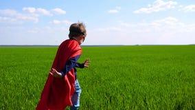 Ένα παιδί έντυσε καθώς ένας υπεράνθρωπος τρέχει πέρα από έναν πράσινο τομέα μια ηλιόλουστη ημέρα απόθεμα βίντεο