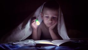 Ένα παιδί διαβάζει ένα βιβλίο κάτω από τα καλύμματα με έναν φακό τη νύχτα αγόρι με την ελαφριά τρίχα και τα μπλε μάτια φιλμ μικρού μήκους