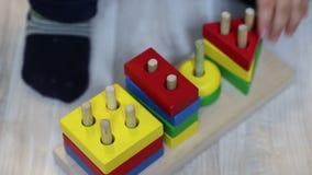 Ένα παιδί ενός έτους βρεφών βάζει τις γεωμετρικές μορφές στην καρφίτσα στην ξύλινη κατασκευή Κινηματογράφηση σε πρώτο πλάνο του χ απόθεμα βίντεο