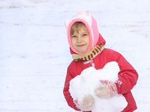 Ένα παιδί εξετάζει τη κάμερα, χιόνι, στα χέρια του μια χιονιά, σε ένα κλίμα του άσπρου χιονιού Στοκ Εικόνα